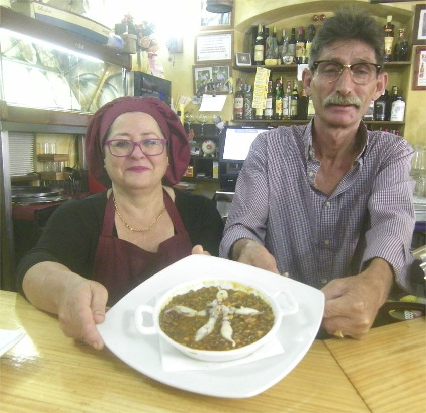 Ana María Riquet y Juan José Benitez, los propietarios del Nuevo Echate Payá, posan con el plato de lentejas con puntillitas, una de sus tapas más famosas. Foto: Cosasdecome