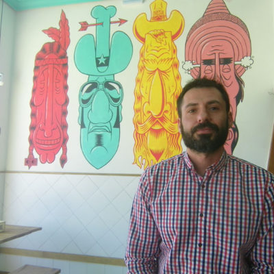 """Carlos Rivas, uno de los socios que ponen en marcha Sara River posa delante de un cuado alusivo a la chirigota """"Los comboys da pejeta"""". Foto: Cosasdecome"""