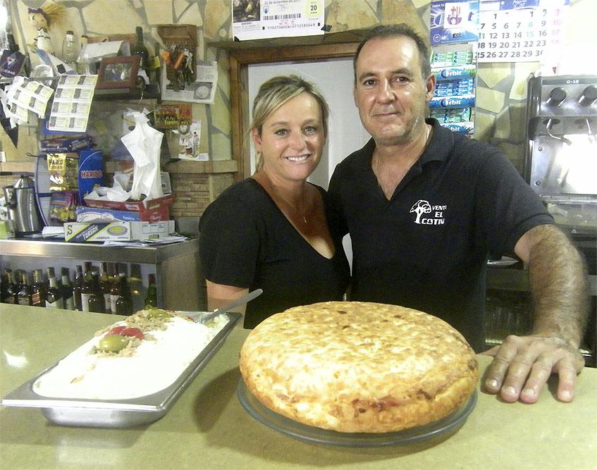 Inma Butrón posa junto a su marido Jesús Oliva con dos de las estrellas de la casa, la ensaladilla y la tortilla de bacon y queso. Foto: Cosasdecome