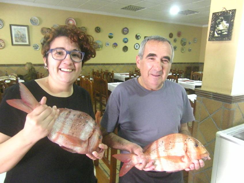 Juan Osorio y su hija Tamara con dos de los pescados que sirven en su establecimiento. Foto: Cosasdecome