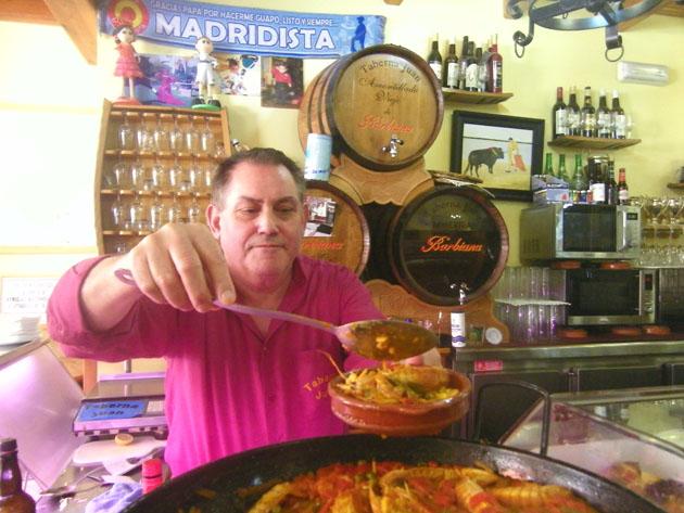 Juan Ramos, conocido como Juan Barbiana, sirve una tapa de arroz en su establecimiento.