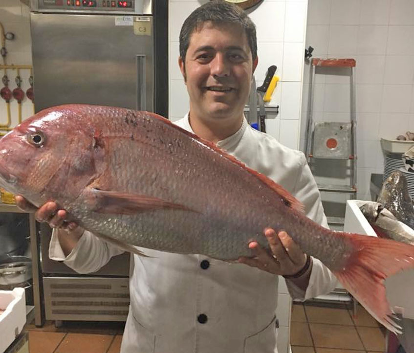 El cocinero Marco Antonio López con uno de los pescados de roca que ofrecen habitualmente en el establecimiento.