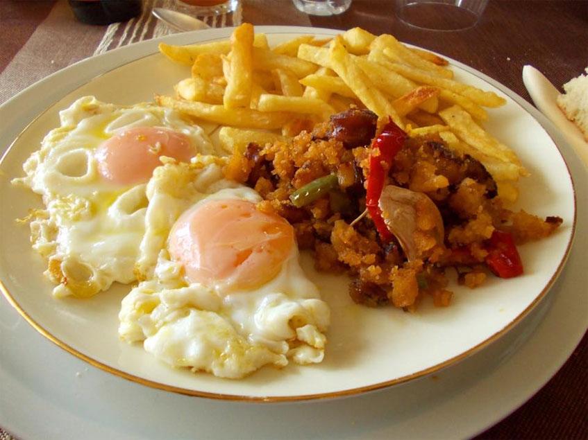 Los huevos fritos con papas y migas fotografiados por Los Papafritas.
