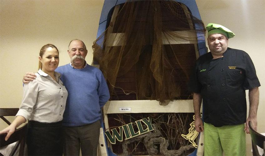Cristina y Antonio López junto al cocinero Paco Navarro. Los tres en uno de l os comedores del Willy que preside una barca. Foto: Cosasdecome