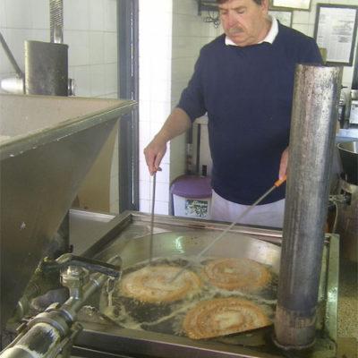 Alfonos Orellana friendo sus ruedas de churros. Foto: Cosasdecome
