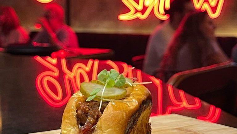 Brioche a la mantequilla tostada, pato confitado, salsa show y encurtido de Tiemar