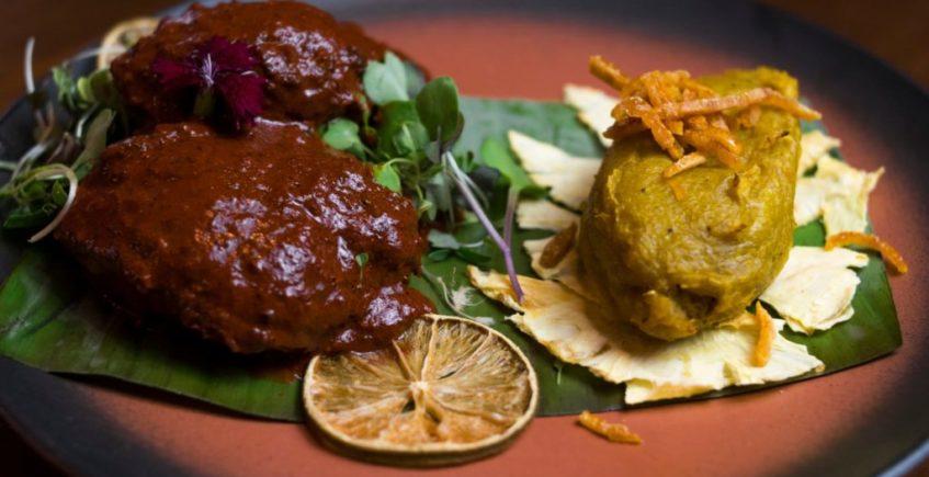 Cochinita pibil con una salsa piri-piri acompañado de un plátano macho frito envuelto en su misma hoja de Xuumil