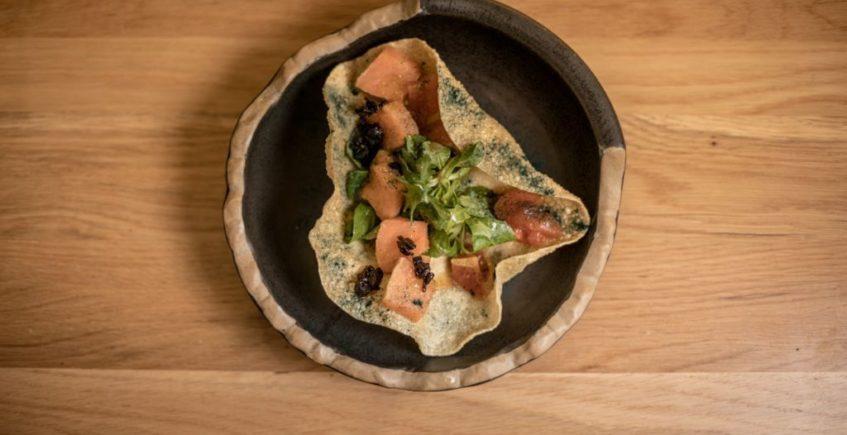 Crujiente de salmón fresco, madurado con técnica japo en alga kombu, tomates al jengibre y ajo negro de la Barra de Rosario