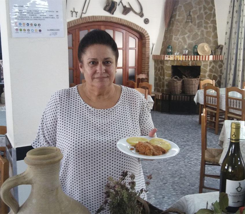 Antonia Macho Rodríguez, una de las hijas de los fundadores de la venta, posa con un plato de conejo que servirán en los días de la feria. Foto: Cosasdecome