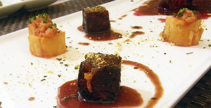 Las manittas de cerdo, transformadas en unos cubos que tienen una textura que recuerda al foie se alternan con otros tacos de patata frita rellenos de salsa romescu. Son las guarniciones de unos tacos de pato. Foto: Cosasdecome.