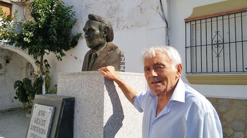 El cantaor flamenco y fundador del bar Rufino, Rufino García, posa junto al monumento dedicado a él que hay en el centro de Paterna. Foto: Cosasdecome