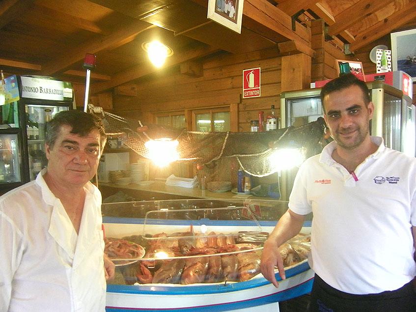 Juan Manuel Laza González y su hijo Juan Manuel Laza Aviles de Casa Mane, junto a la barca donde tienen expuestos los pescados. Foto: Cosasdecome