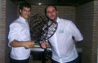 Los cocineros Carlos Hernández, jefe de cocina, y Eduardo Pérez, parrillero, portan las besugueras en las que asan los pescados en Cataria. Foto: Cosasdecome.
