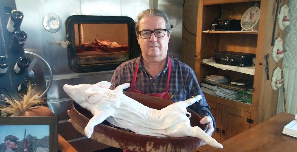 Sebastián Sánchez Cabeza con un cochinillo preparado para meter en el horno. Foto: Cosasdecome