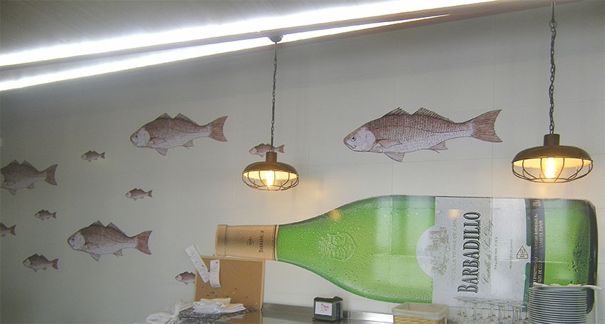 Así es la decoración del restaurante La Lonja. Por las paredes nadan unas corvinas y hasta una botella de Barbadillo. Foto: Cosasdecome