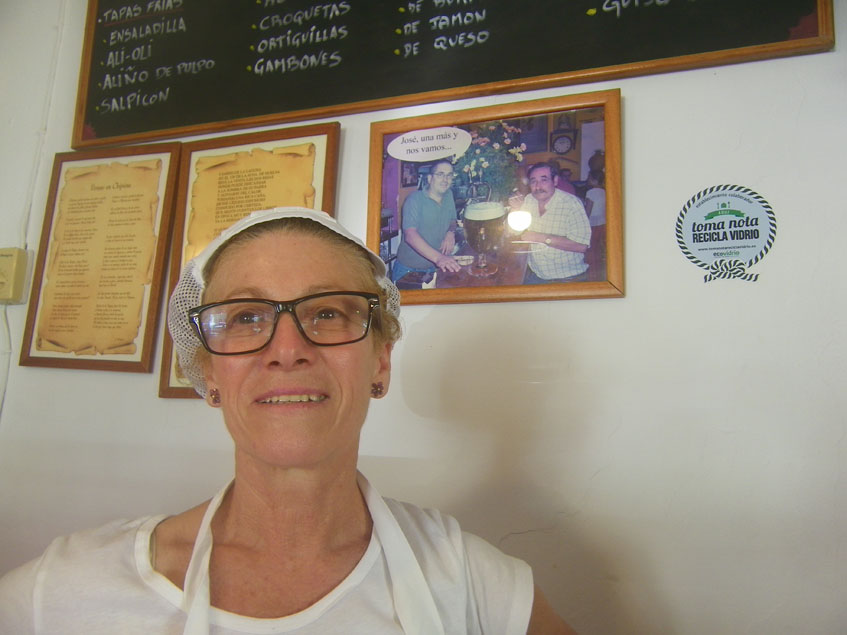 Mari Carmen Letrán en su bar Las Dos Rejas de Chipiona. Detrás aparece una foto en la que está su marido, José Rafoso (con camisa blanca) que gestionó con ella el bar desde 1996. Foto: Cosascome.