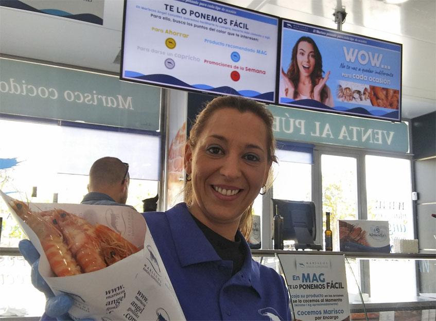 Una empleada de la firma muesta un cartucho de langostinos recien cocidos. Foto: Cosasdecome
