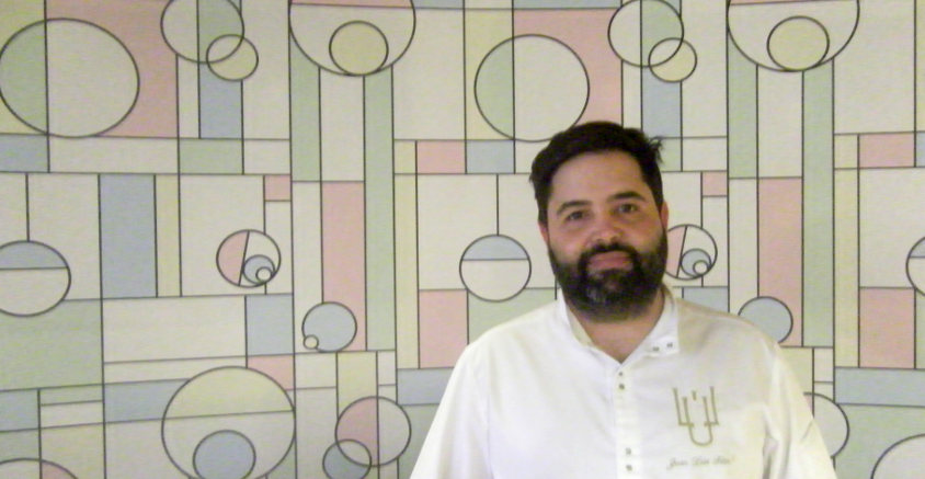 Juan Luis Fernández delante de la pared del nuevo comedor, decorado con colores pastel formando figuras geométricas. Foto: Cosasdecome