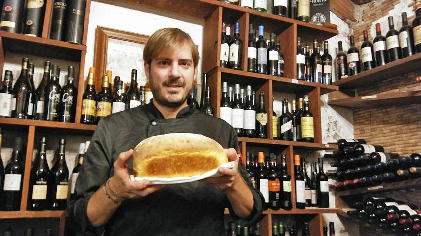 Javier Muñoz el jefe de cocina de La Carboná en la bodega de su restaurantes posando con un pan que realiza con velo de flor. Foto: Cosasdecome