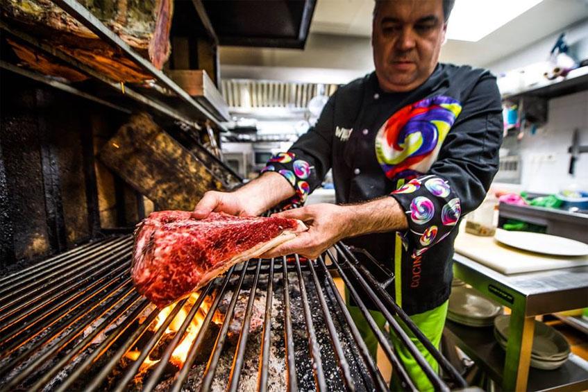 El cocinero Paco Navarro coloca un trozo de carne sobre la parrlla. Foto: Cedida por el establecimiento