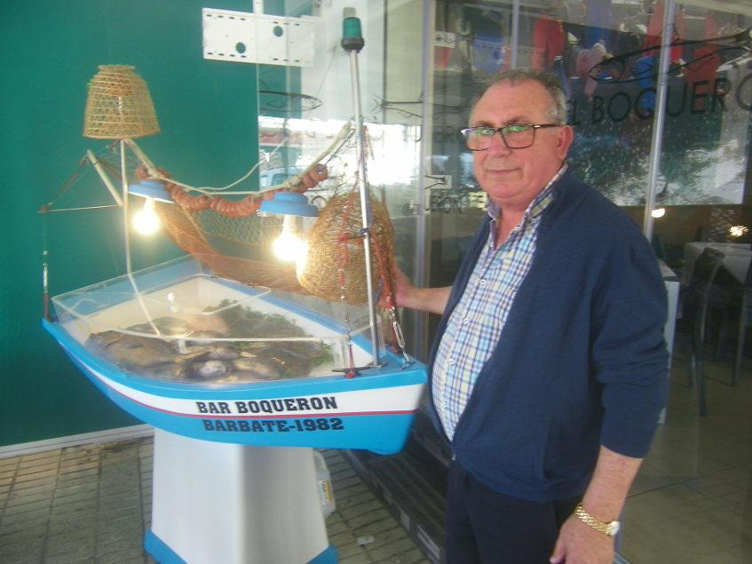 Enrique Revuelta junto a su barca exposición de pescados del bar Boquerón de Barbate. Foto: Cosasdecome
