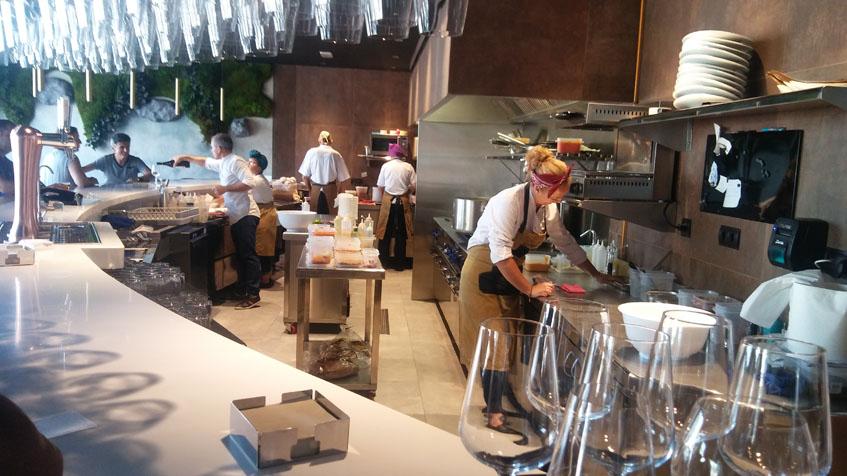 Desde la barra se ve como trabajan en la cocina. Foto: Cosasdecome