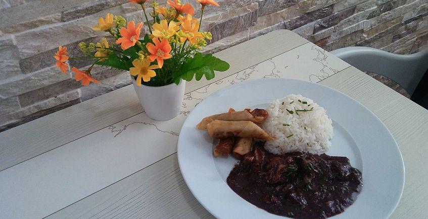 Un plato combinado con dos de las especialidades, lumpia y Sizzling Sisig, con arroz.