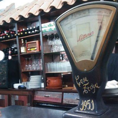 La barra del bar Pepe Troya. El establecimiento mantiene objetos antiguos como este peso que preside la barra o las estanterias, que funcionaban ya cuando era almacén a mediados del siglo XX. Foto: Cosasdecome